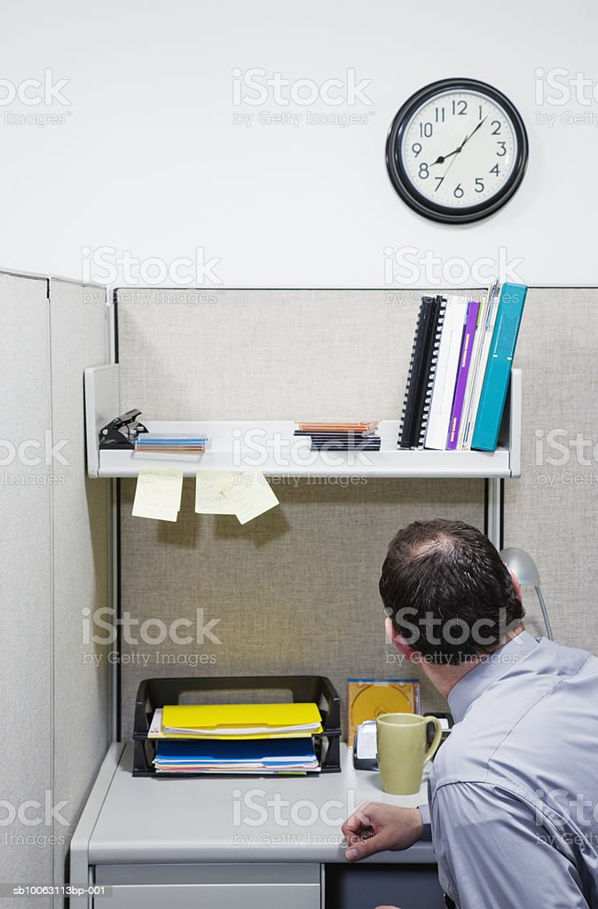Businessman sitting in office looking at clock foto de stock royalty-free