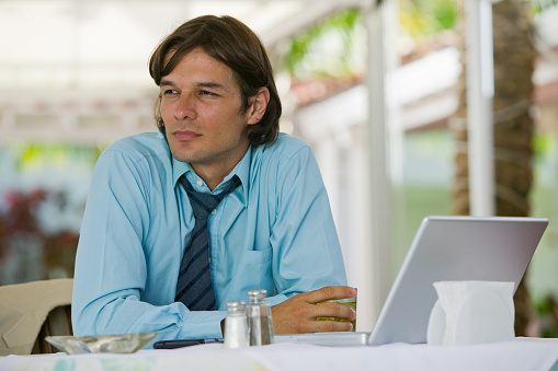 Businessman sitting in outdoor restaurant having a drink with laptop computer