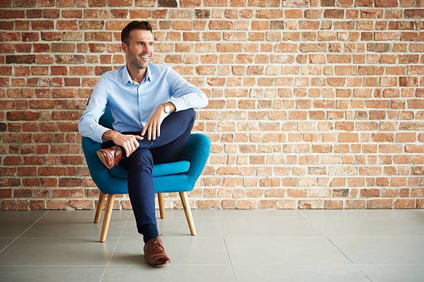 Businessman sitting in the armchair Businessman sitting in the armchair cross legged stock pictures, royalty-free photos & images