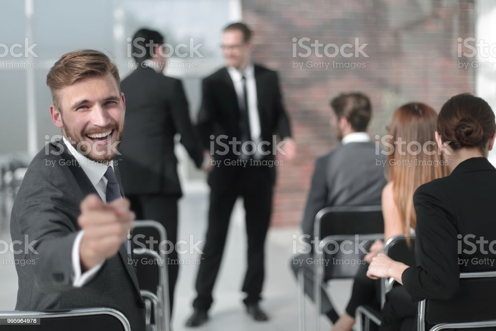 businessman sitting in the conference room, pointing at you stock photo