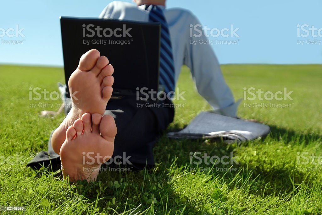 Businessman Sitting in the Grass with Bare Feet royalty-free stock photo