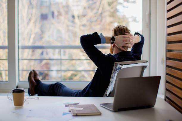 businessman sitting in the office and looking through the window - mani dietro la testa foto e immagini stock