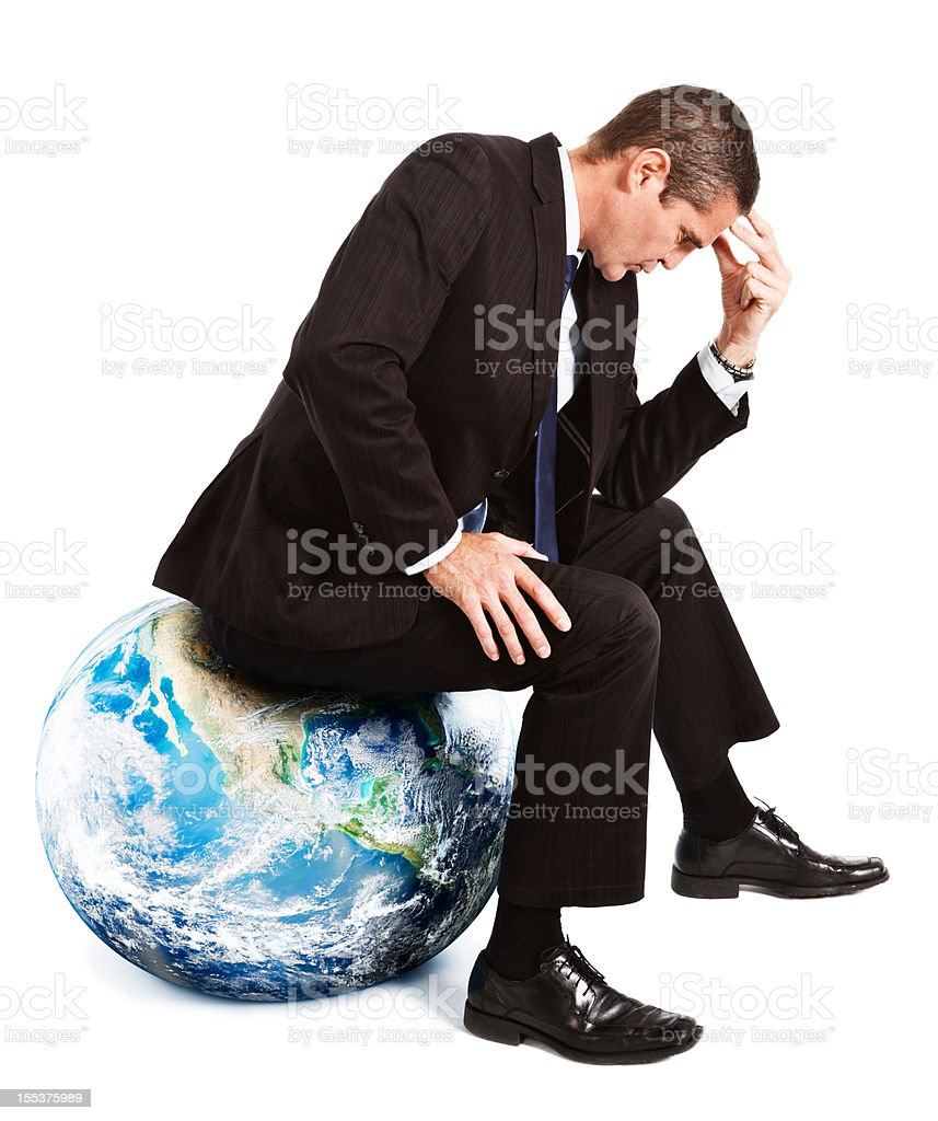Businessman sitting in Thinker pose on Earth globe stock photo