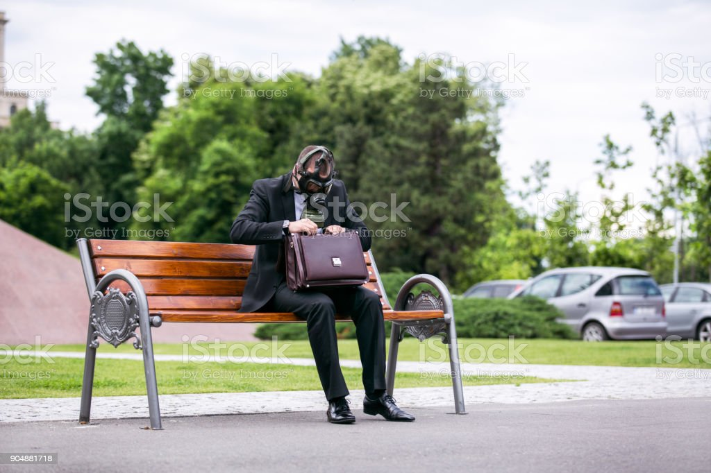 Businessman sitting on a banch wearing a gas mask looking in the briefcase stock photo