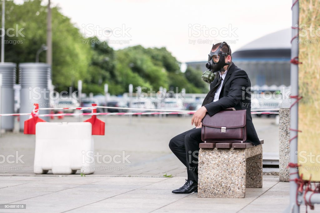 Businessman sitting on a banch with briefcase wearing a gas mask stock photo