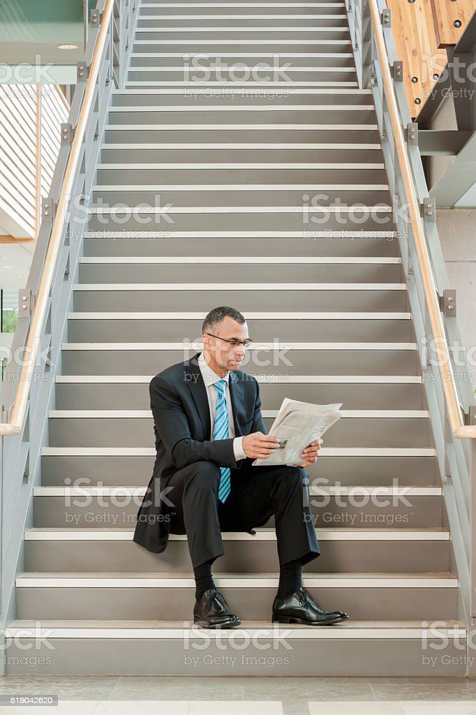 Businessman sitting on a stairway reading a paper stock photo