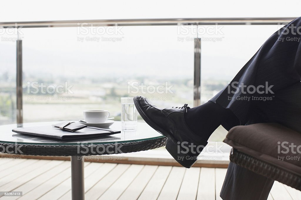 Businessman sitting on balcony royaltyfri bildbanksbilder