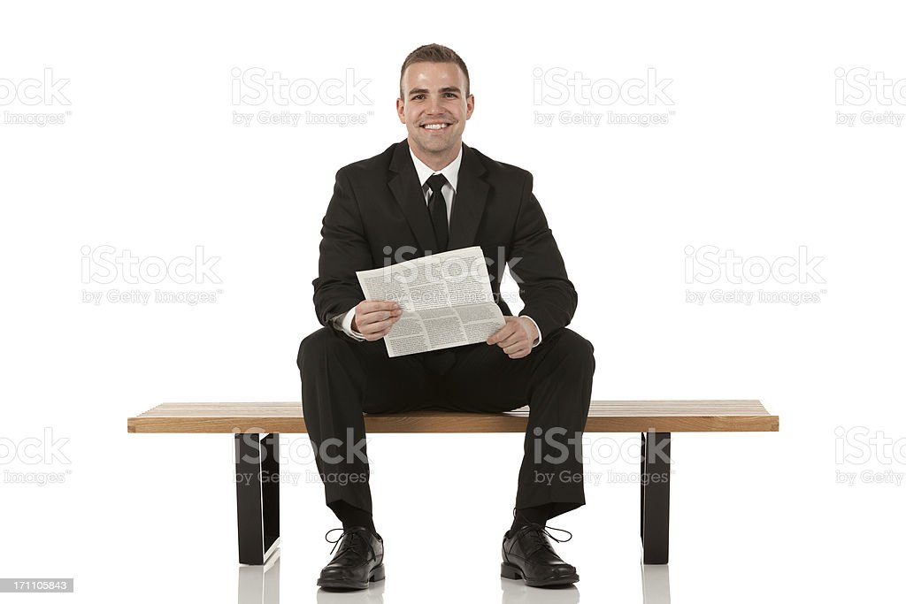 Businessman sitting on bench and holding a newspaper royalty-free stock photo