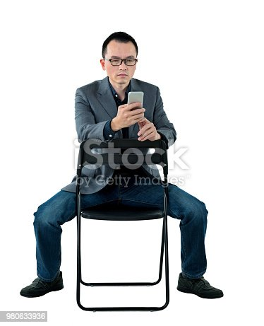 istock Businessman sitting on chair and using mobile phone 980633936