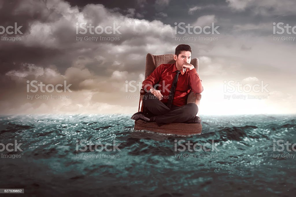 Businessman sitting on chair in the middle of the sea stock photo