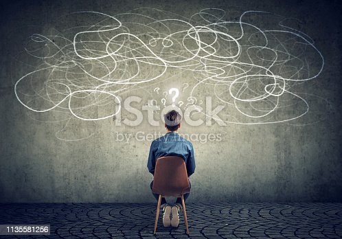 istock businessman sitting on chair looking at a scribble on a wall feeling confused 1135581256