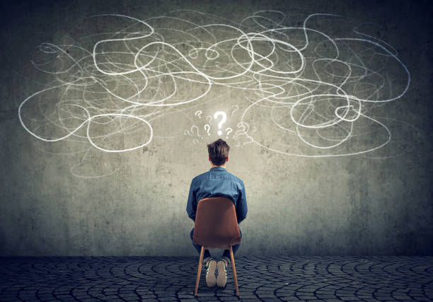 businessman sitting on chair looking at a scribble on a wall feeling confused Back view of a thoughtful young businessman sitting on chair looking at a scribble on a wall feeling confused with too many questions decisions stock pictures, royalty-free photos & images
