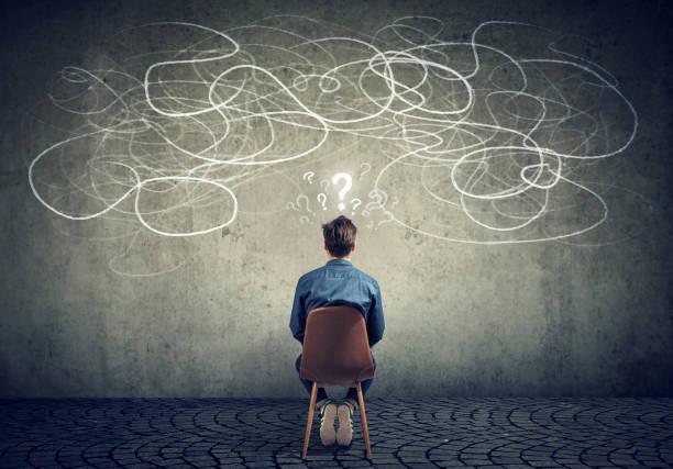 zakenman zittend op de stoel te kijken naar een krabbel op een muur gevoel verward - negatieve emotie stockfoto's en -beelden