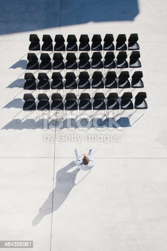 istock Businessman sitting on chair looking at lines of empty office chairs 484355061