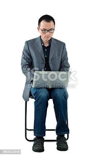 istock Businessman sitting on chair with a laptop 980633948