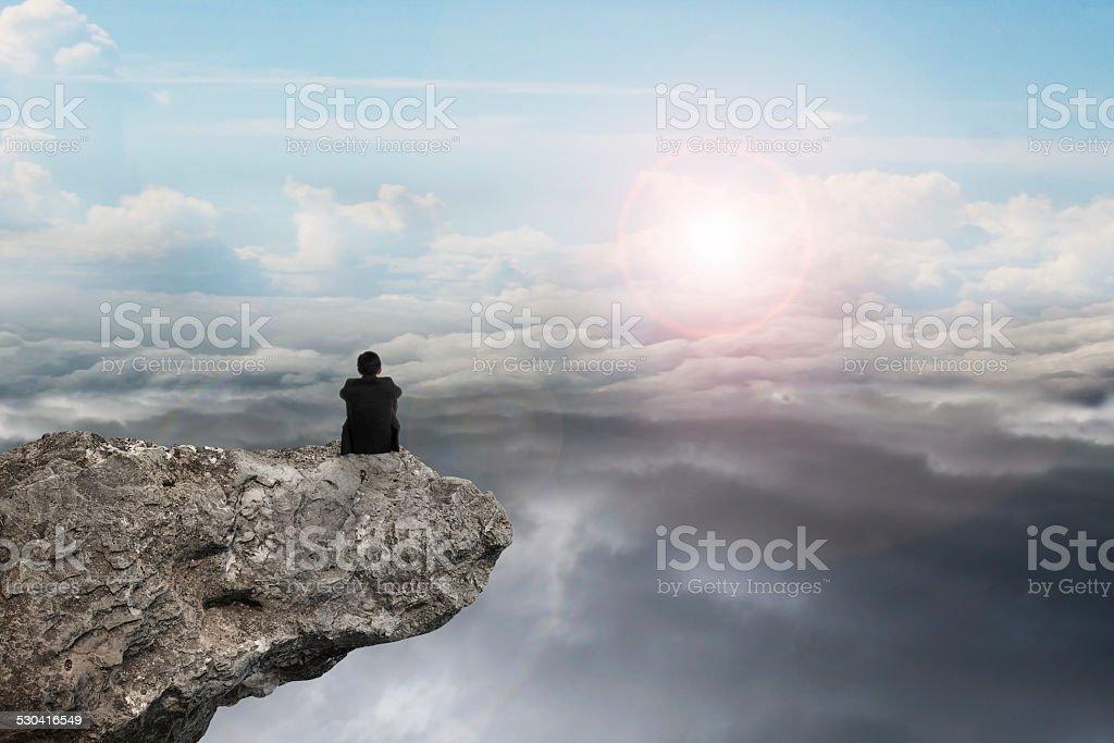 Geschäftsmann sitzt auf Klippe mit natürlichem Tageslicht cloudscap sky – Foto