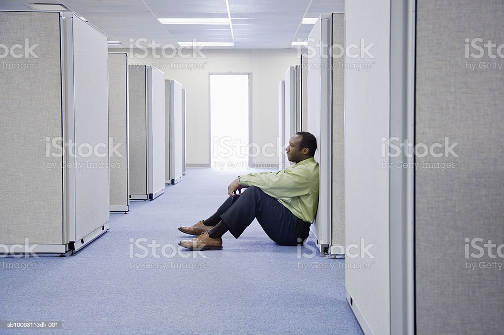Businessman sitting on floor between office cubicles, side view royalty-free stock photo