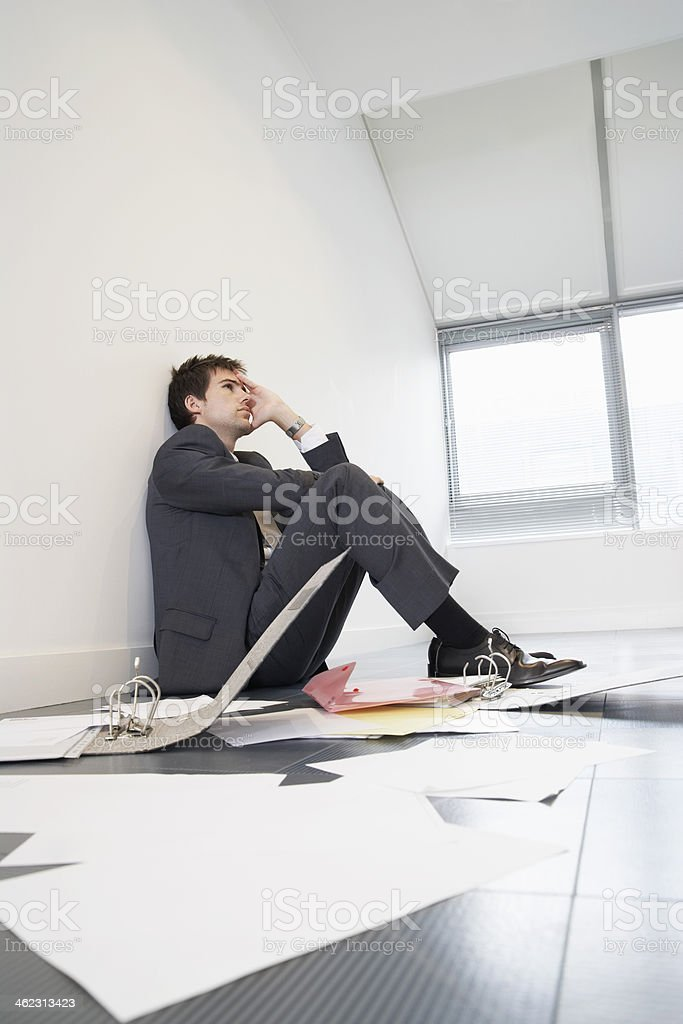 Businessman Sitting On Floor By Scattered Files stock photo