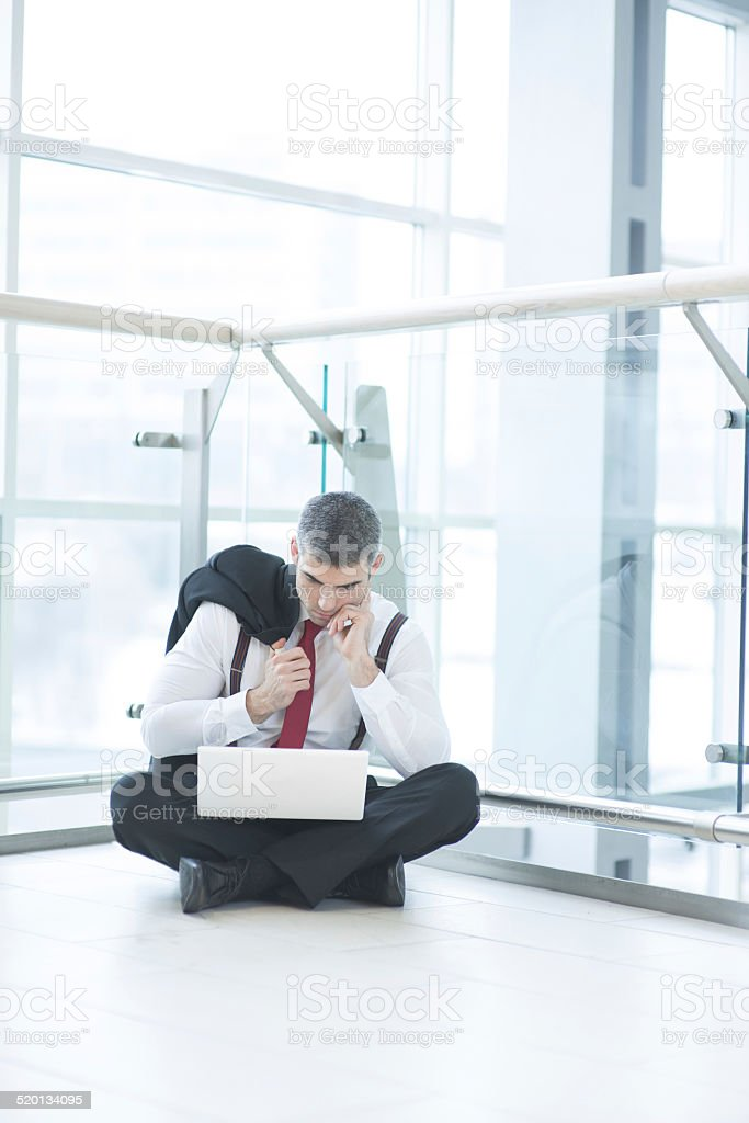 Businessman sitting on floor using laptop royalty-free stock photo