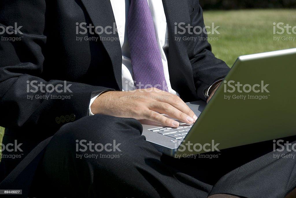 Businessman sitting on grass using laptop royalty-free stock photo