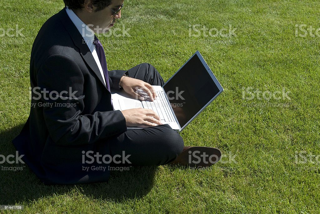 Businessman sitting on grass using laptop, Turkey, Istanbul, Zekeriyaköy royalty-free stock photo