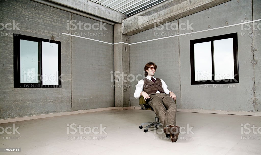 Businessman Sitting on Office Chair in Empty Room royalty-free stock photo