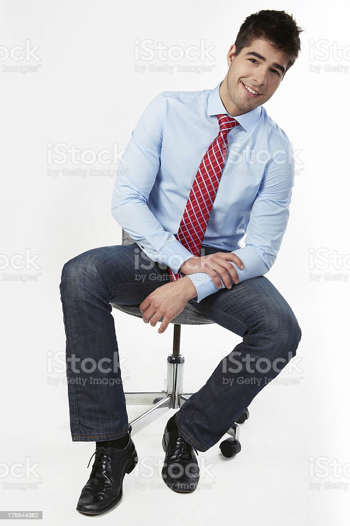 Businessman sitting on office chair smiling stock photo