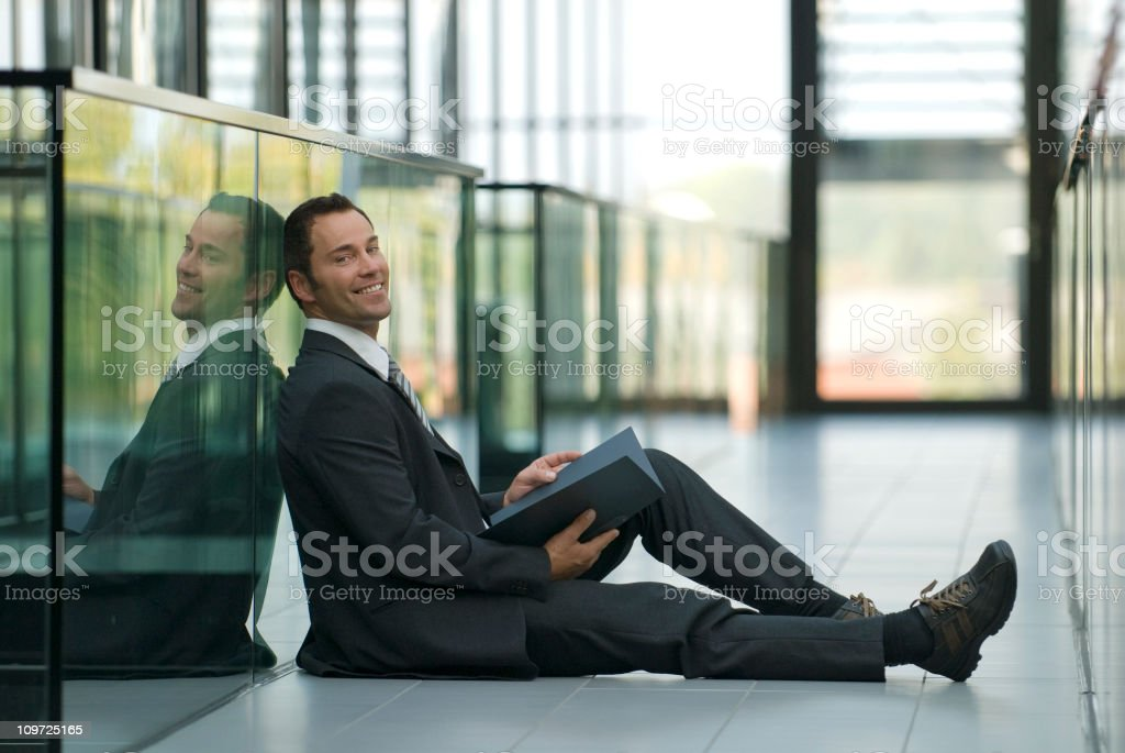 Businessman Sitting on Office Floor and Smiling royalty-free stock photo