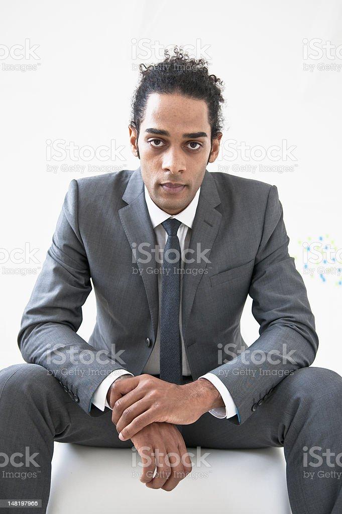 Businessman sitting on ottoman royalty-free stock photo
