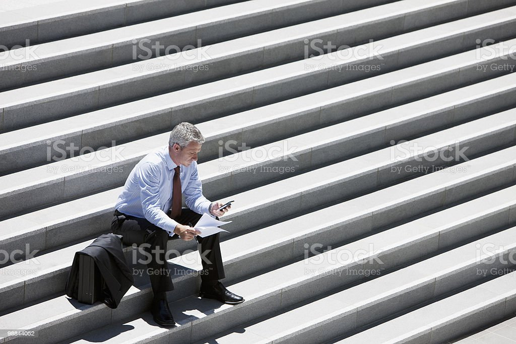 Businessman sitting on outdoor steps and text messaging royalty-free stock photo