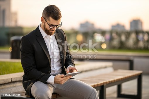 Happy businessman sitting on park bench and working
