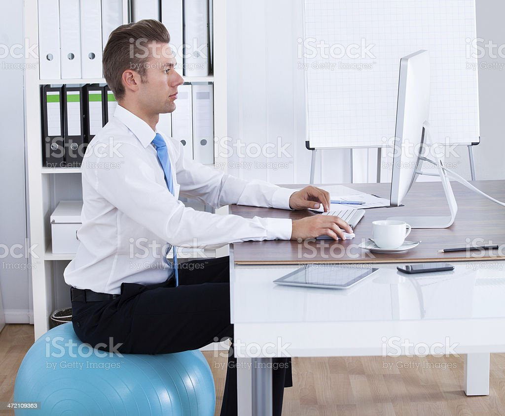 Businessman Sitting On Pilates Ball And Using Computer stock photo