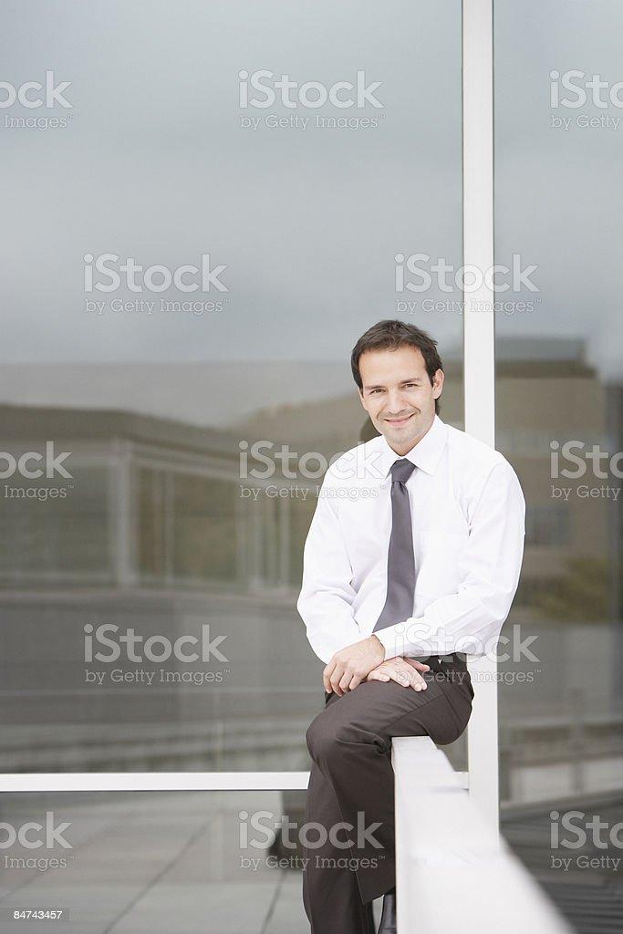 Homme d'affaires, assis sur la balustrade photo libre de droits