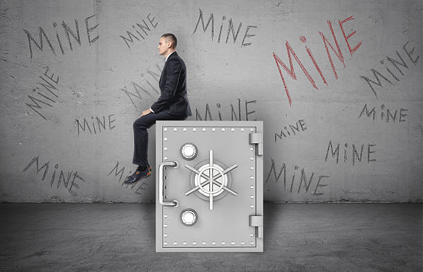 businessman sitting on safe and background of wall with inscription - hoarding stock photos and pictures