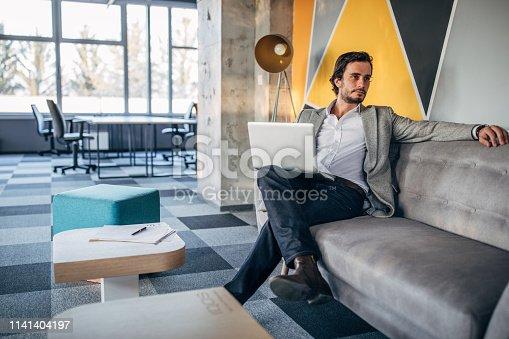 530281733istockphoto Businessman sitting on sofa in modern office 1141404197