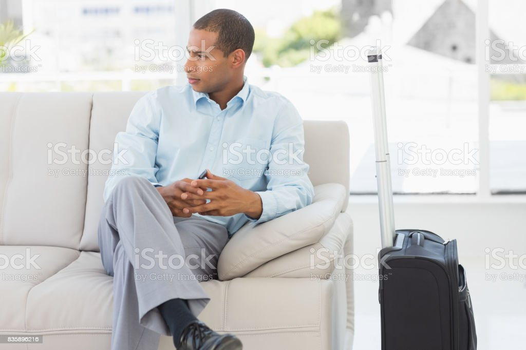 Businessman sitting on sofa waiting to depart on business trip stock photo