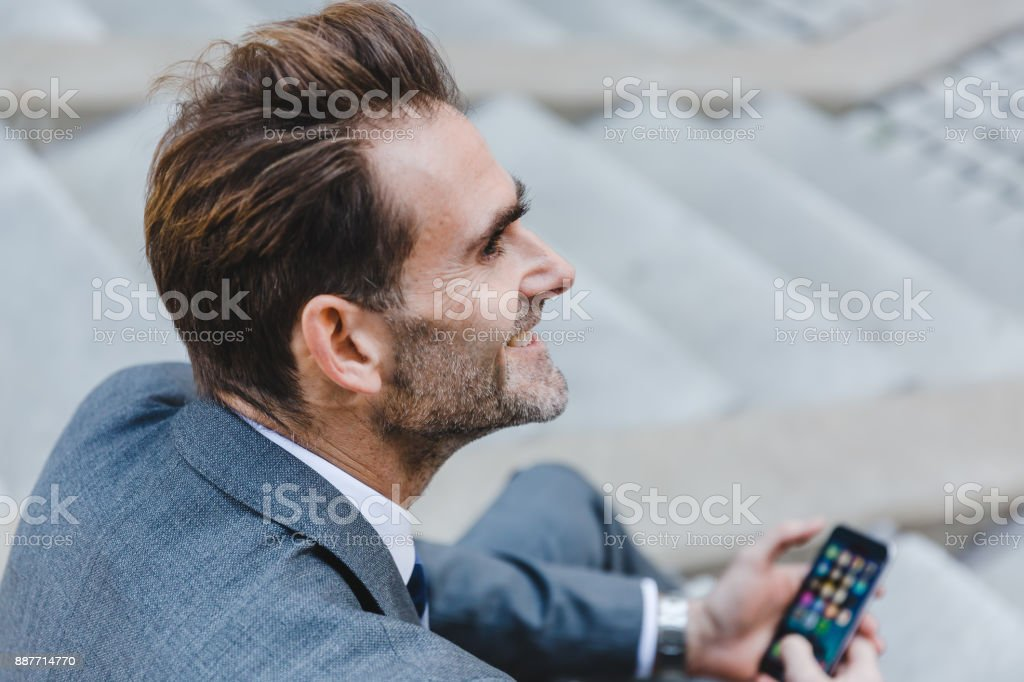 businessman sitting on stairs in an office park with a smartphone in...
