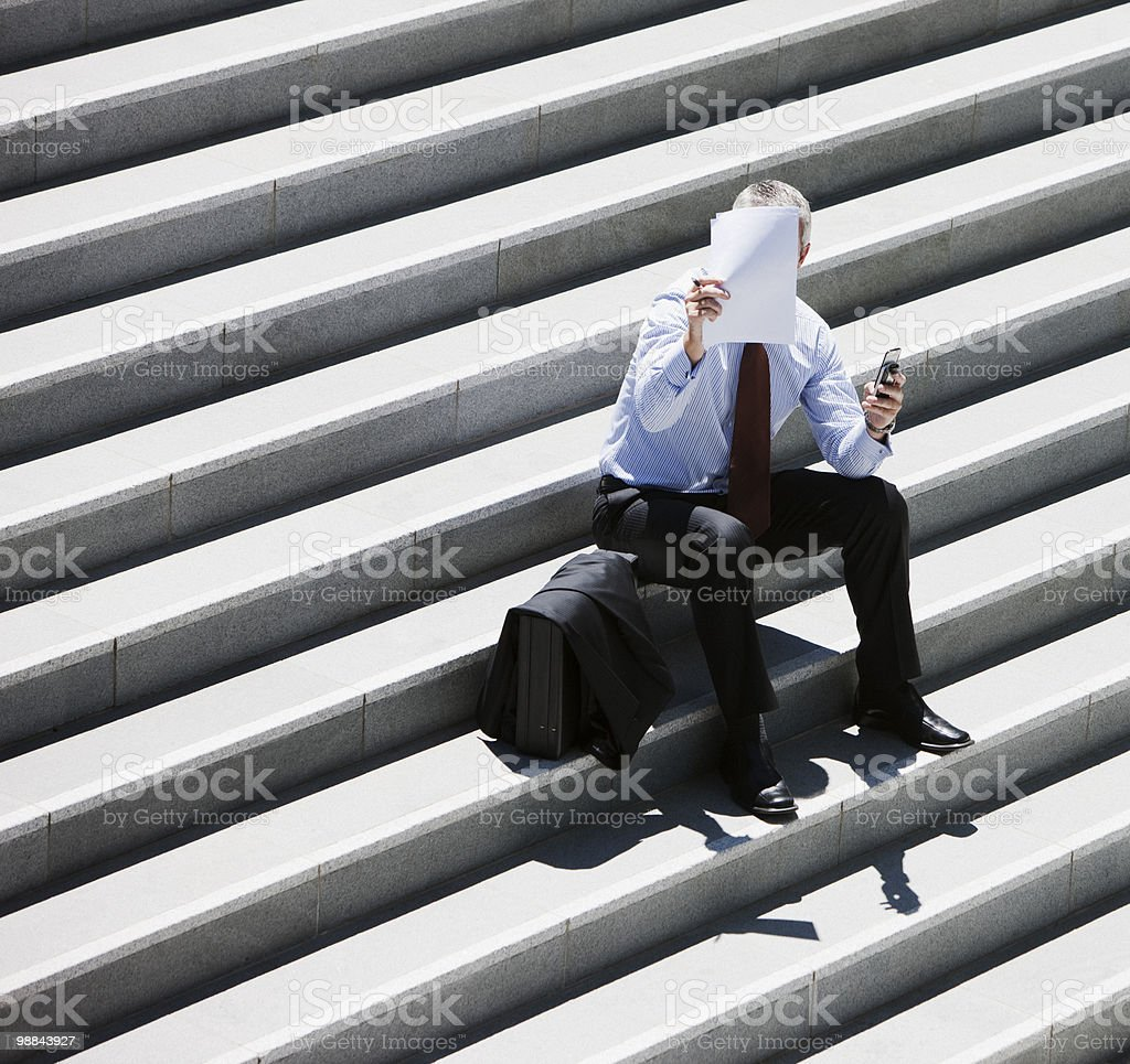 Businessman sitting on steps looking at paper 免版稅 stock photo