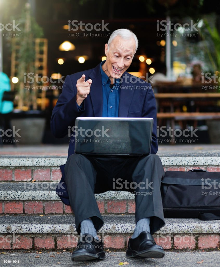 Businessman sitting on steps rejoices at news on his laptop PC stock photo