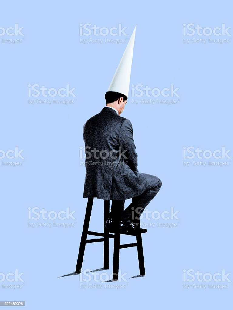 Businessman Sitting On Stool Wearing Dunce Cap stock photo