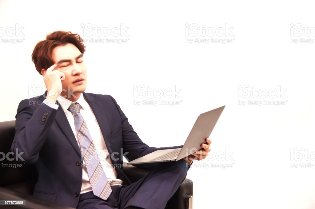 Businessman sitting on the black sofa, thinking hard on making business decision on the internet by laptop computer. stock photo