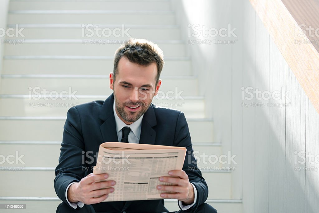 Businessman sitting on the indoor stairs and reading newspaper Portrait of confident businessman wearing dark suit sitting on white stairs in an office and reading a newspaper. 2015 Stock Photo