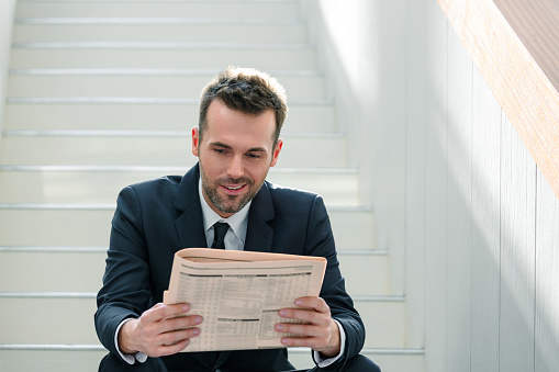 Businessman Sitting On The Indoor Stairs And Reading Newspaper Stock Photo - Download Image Now
