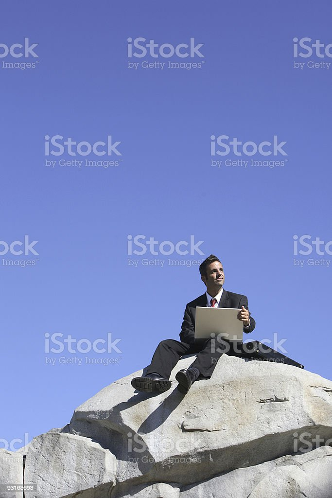 Businessman sitting on top of rock royalty-free stock photo