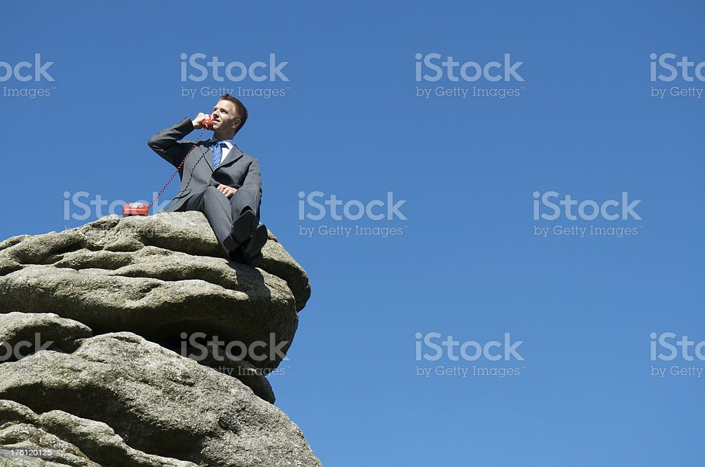Businessman Sitting Outdoors Top of Rock Talking on the Phone royalty-free stock photo