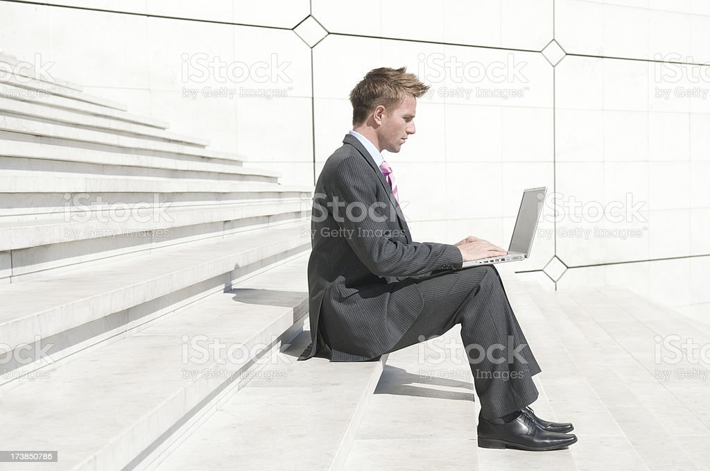 Businessman Sitting Typing Profile Laptop Outdoors White Steps Background stock photo