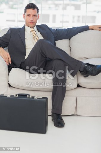 530281723istockphoto Businessman sitting with legs crossed on the couch 827258418