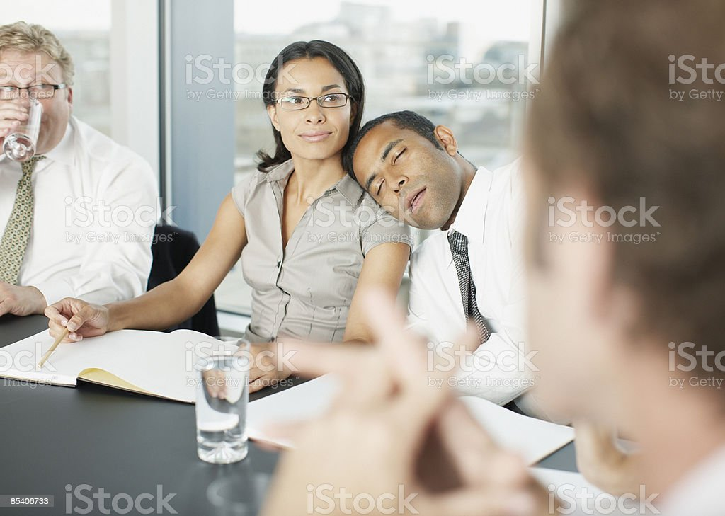 Businessman sleeping during meeting in conference room royalty-free stock photo