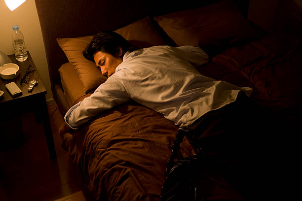Businessman sleeping on bed with suit worn stock photo