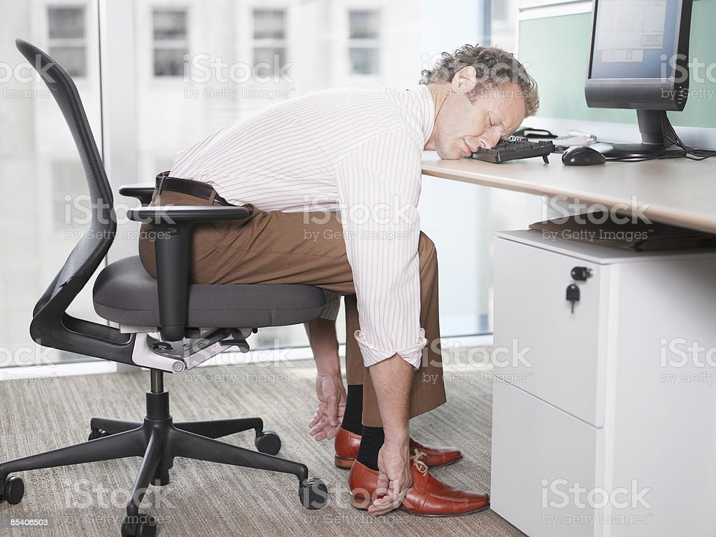 Businessman sleeping on computer keyboard stock photo